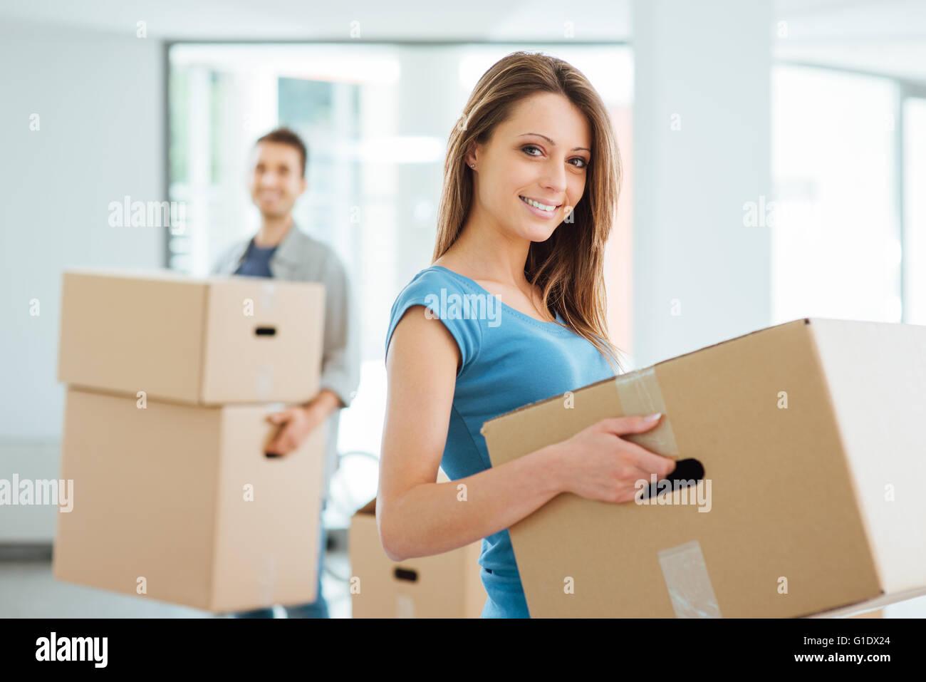Feliz pareja sonriente moviéndose en una nueva casa y llevar cajas de cartón, reubicación y renovación Imagen De Stock