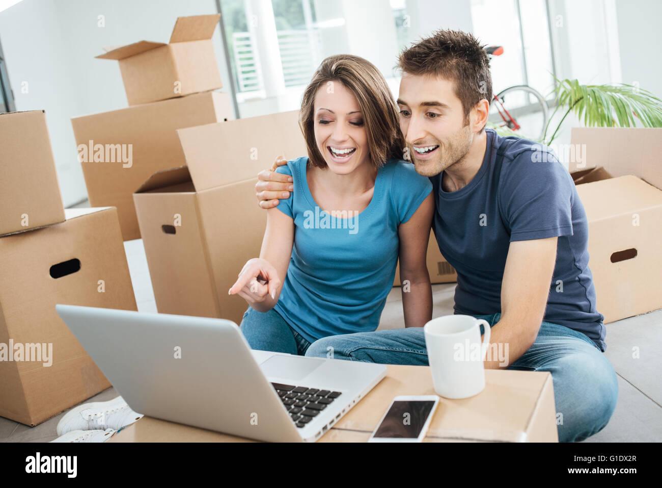 Pareja sonriente sentado en su nueva casa baja rodeado por cajas de cartón, están viendo un video gracioso Imagen De Stock