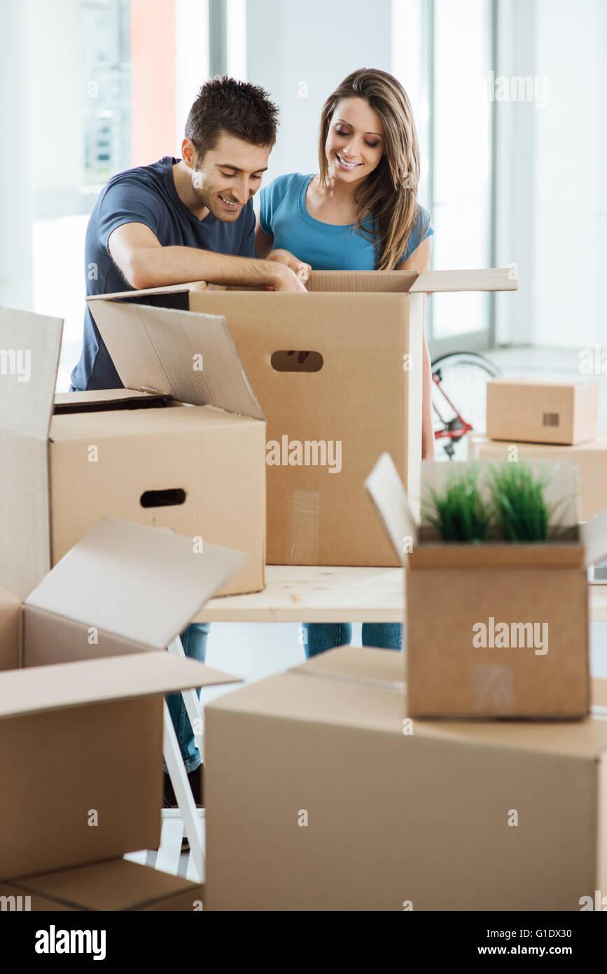 Pareja joven sonriente desembalaje de cajas de cartón en una nueva casa, él está buscando objetos Imagen De Stock