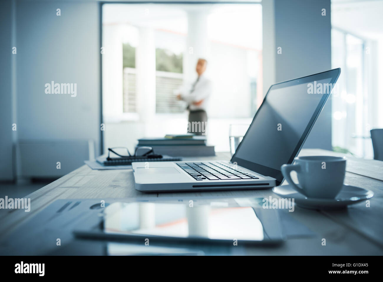 Empresario de pie con los brazos cruzados en su oficina, escritorio con ordenador portátil en primer plano, el enfoque Foto de stock