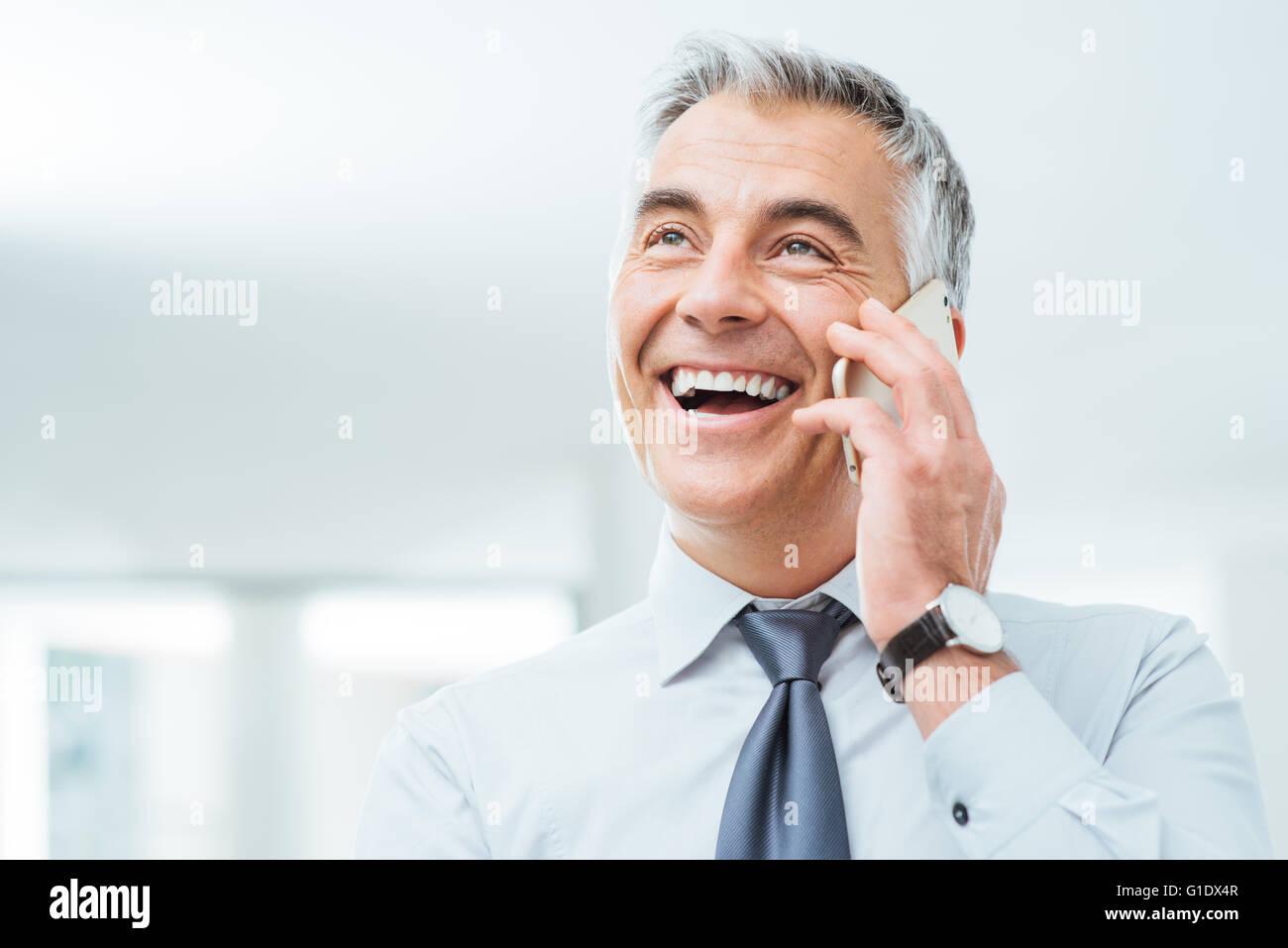 Seguro sonriente empresario tener una llamada en su teléfono inteligente. Foto de stock