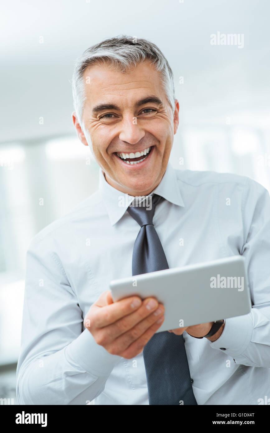 Empresario confiado sonriente mirando a la cámara y el uso de una tableta de pantalla táctil digital Imagen De Stock