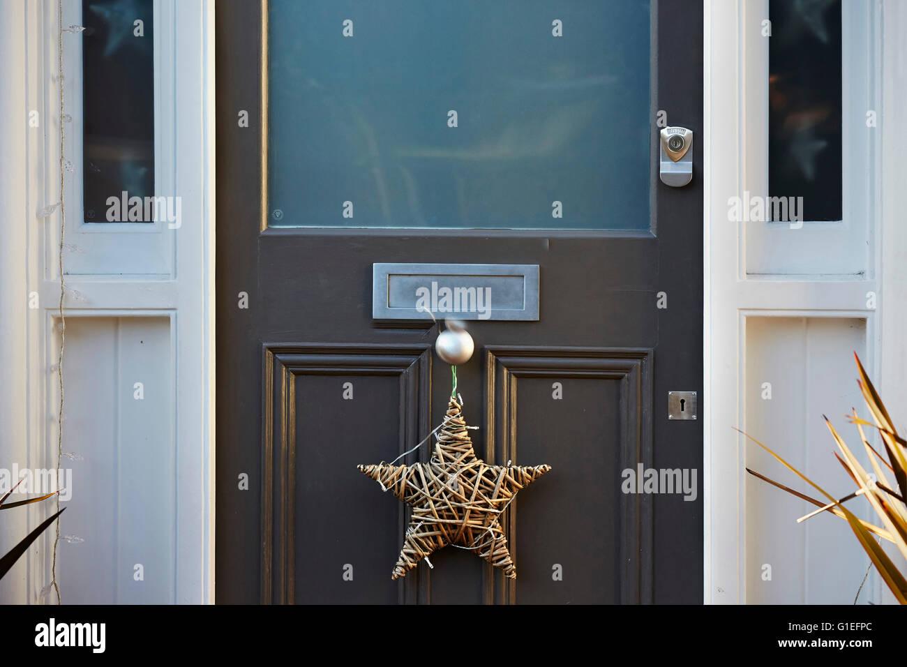 Guirnalda de navidad en la puerta. Guirnalda en forma de estrella colgando del pomo. Imagen De Stock