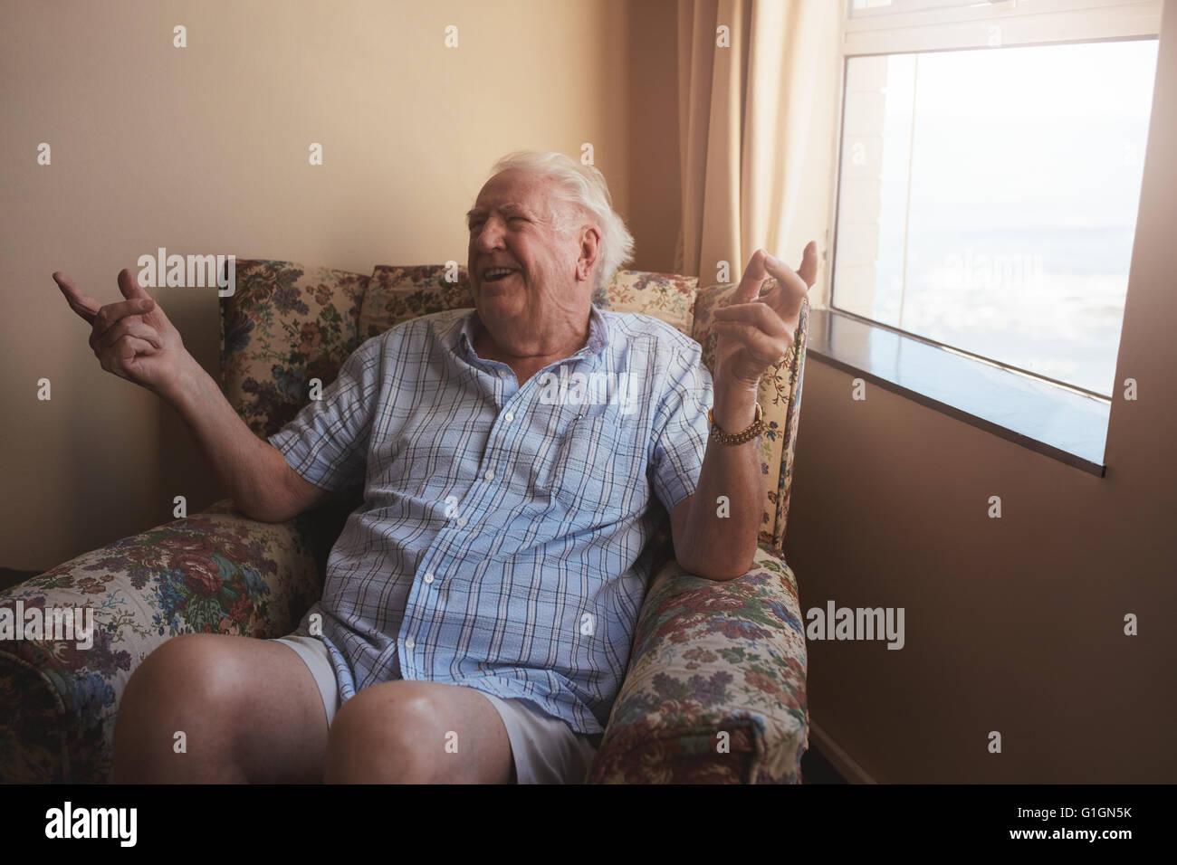 Filmación en interiores de feliz anciano sentado en un sillón y sonriente. Hombre Senior relajante en Imagen De Stock