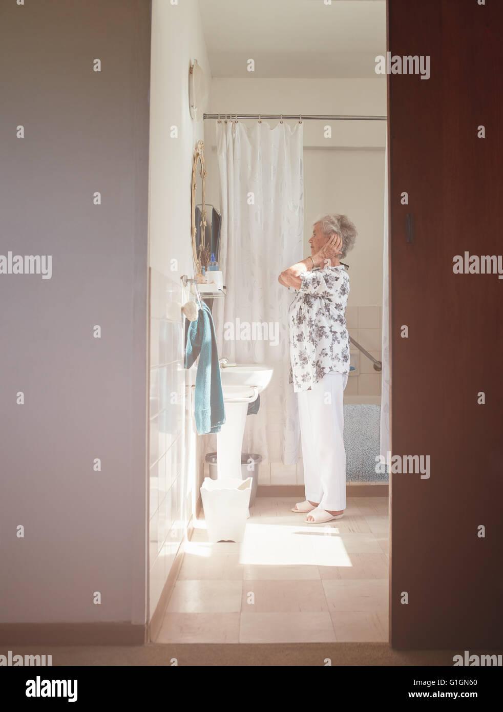 Longitud total interior de disparo anciana alistándose en el tocador. Jefa alistándose en el baño. Imagen De Stock
