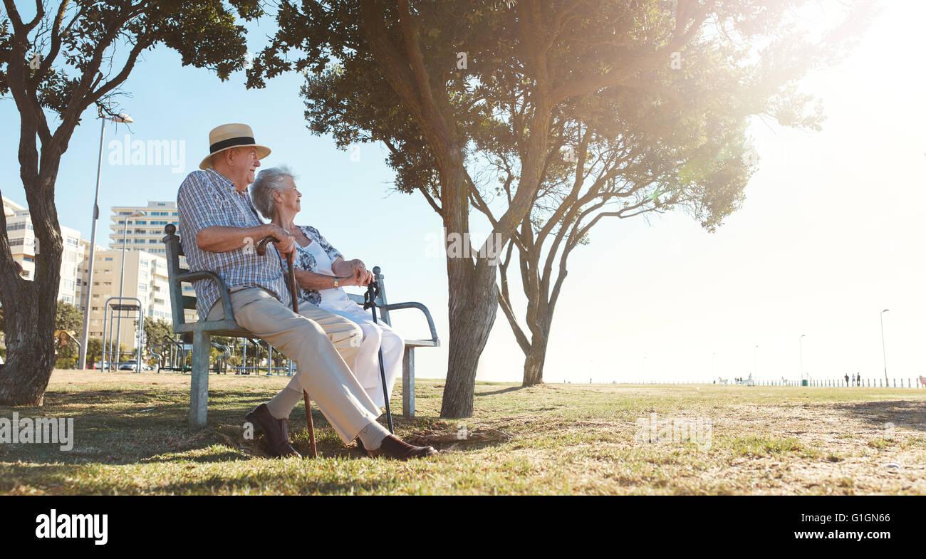 La longitud total de la filmación en exteriores altos pareja sentada en un banco en un día de verano. Imagen De Stock
