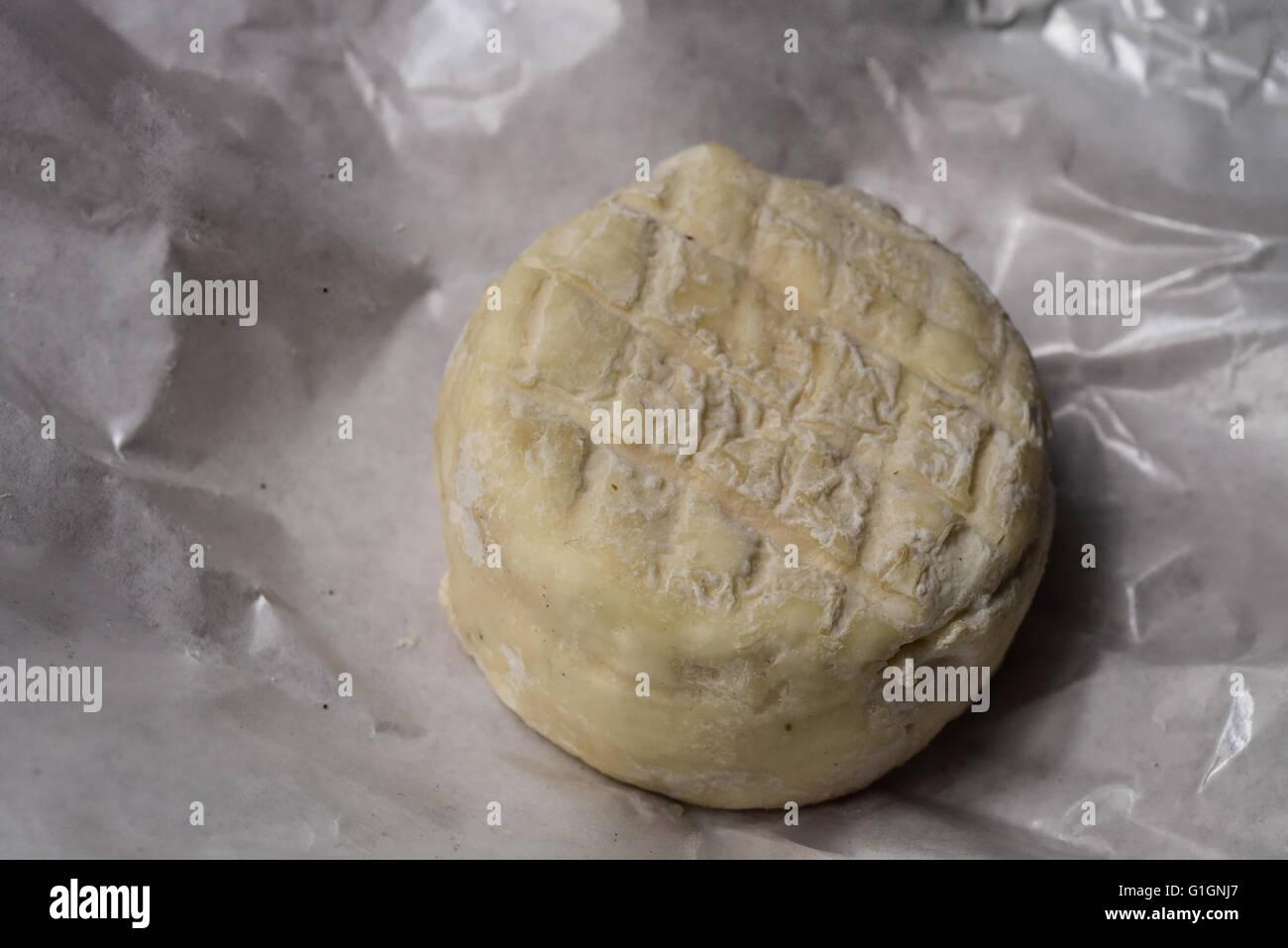 Queso de cabra redondo amarillo en un papel de embalaje Imagen De Stock