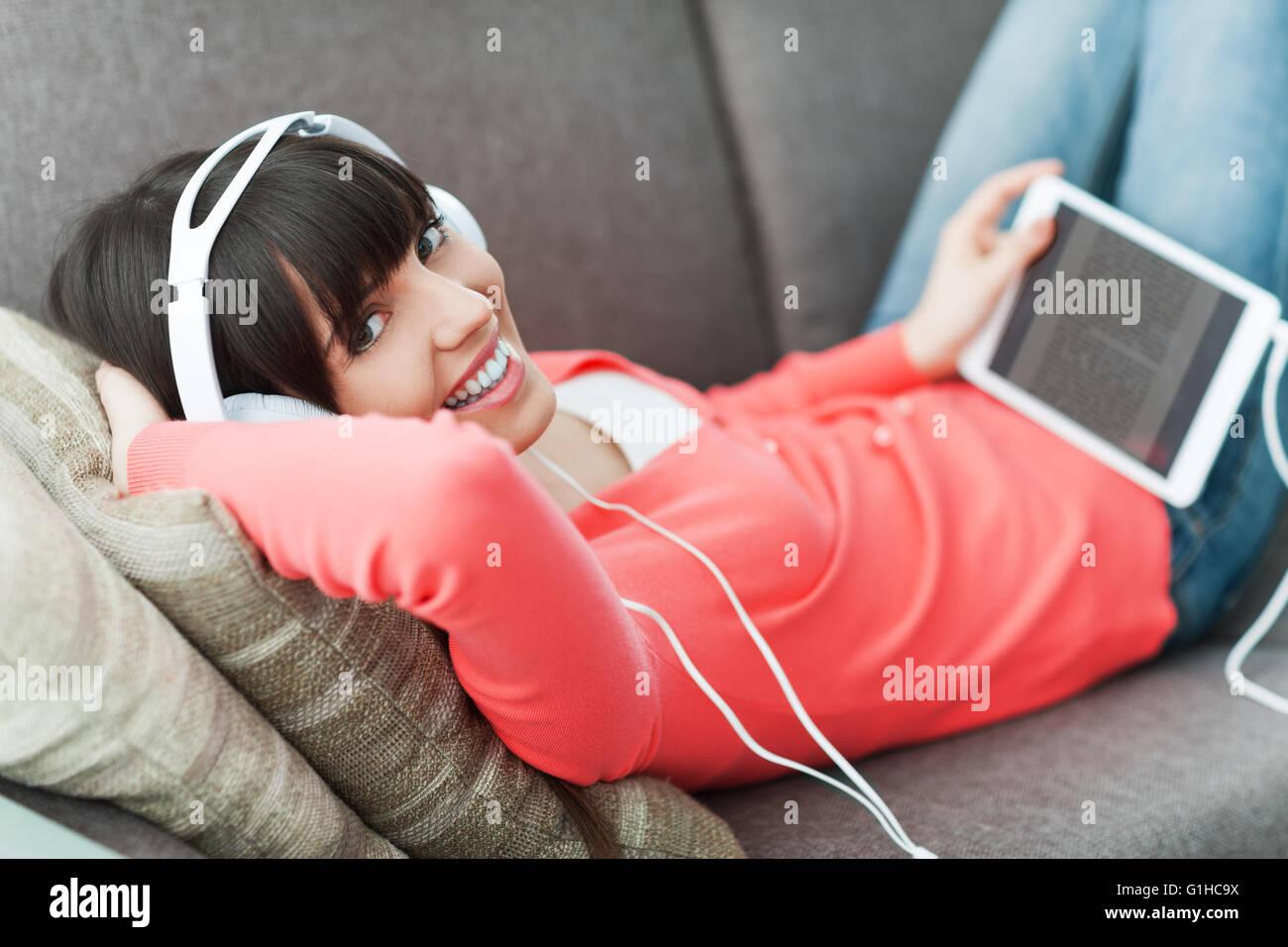 Mujer sonriente relajado en casa en el sofá, ella está usando audífonos, utilizando una tableta digital y ver un Foto de stock