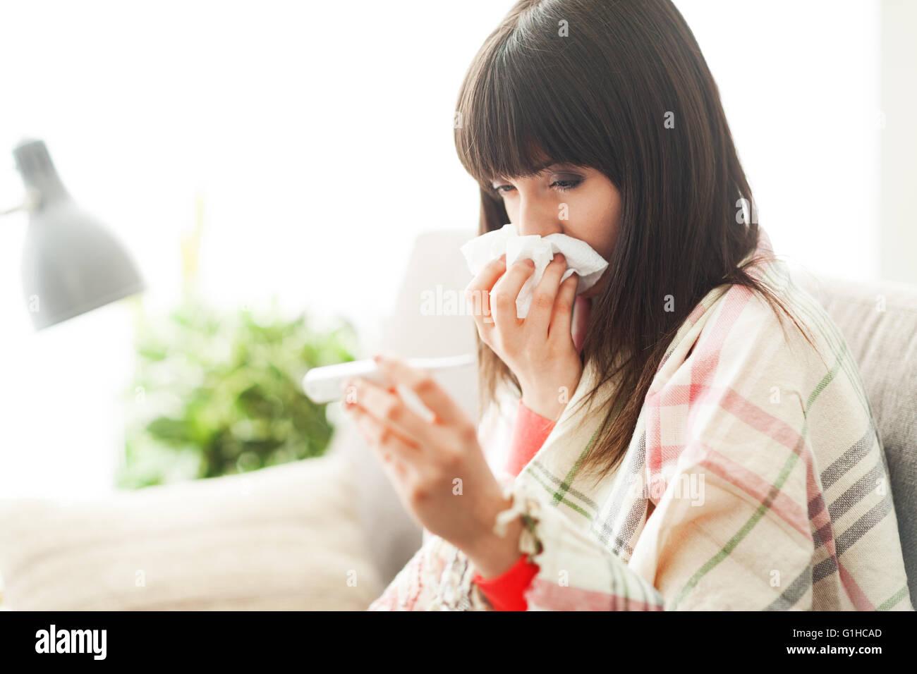 Joven mujer enferma con resfriado y gripe, ella sopla su nariz y medir su temperatura corporal Imagen De Stock