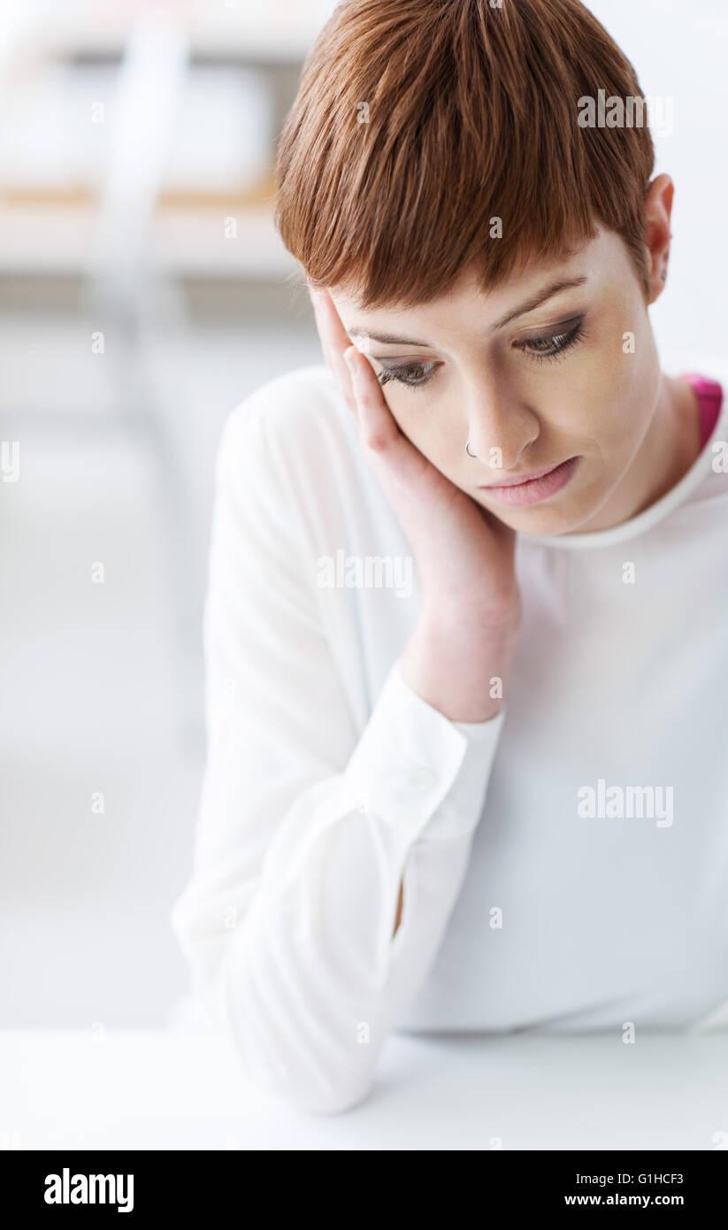 Triste deprimido joven mujer sentada en la mesa y mirando hacia abajo, ella se inclina sobre su mano, dificultades Imagen De Stock