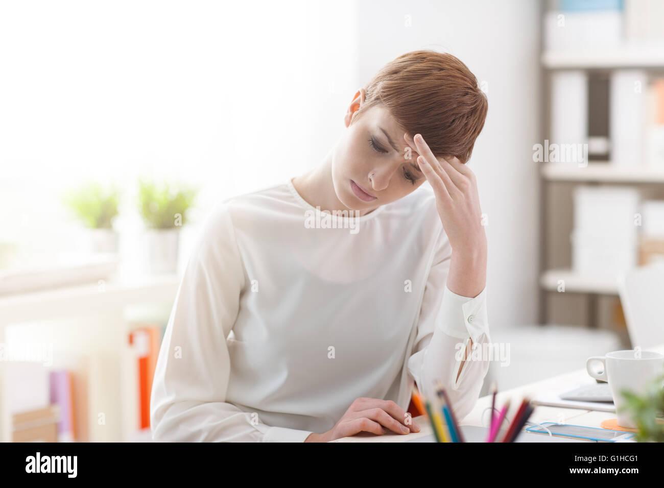 Cansado empresaria sentado en la oficina y tener un dolor de cabeza, ella está tocando su frente, estrés Imagen De Stock