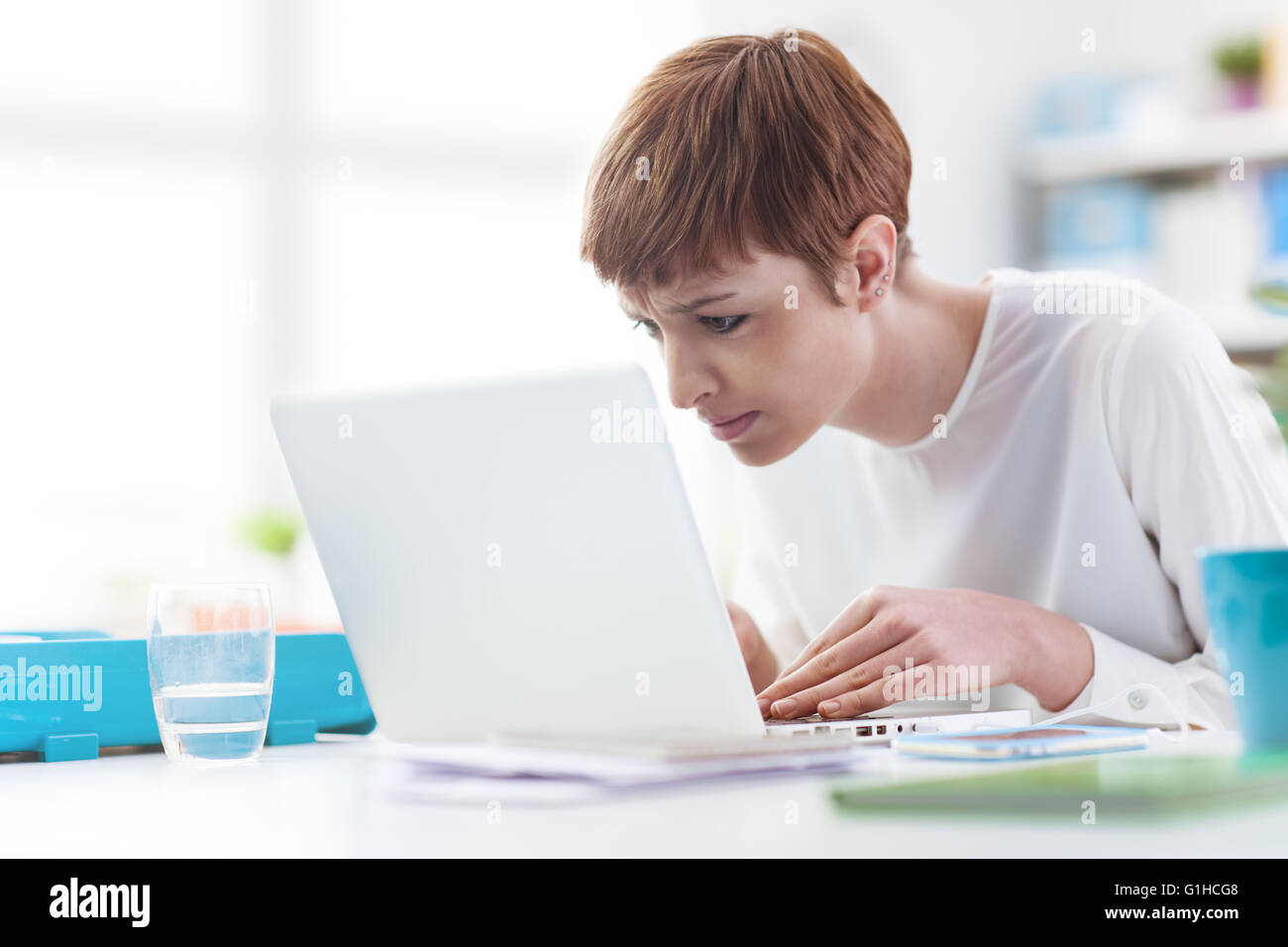 Joven Empresaria trabajando con un portátil, ella se mira demasiado cerca de la pantalla del ordenador, problemas Imagen De Stock