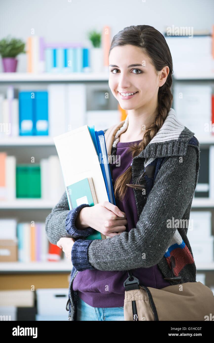 Seguros de estudiante universitario sonriente posando en la biblioteca, ella está sonriendo a la cámara Imagen De Stock