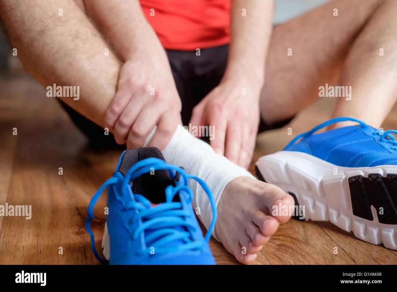 Deportista masajear su tobillo lesionado tras un accidente deportivo Foto de stock