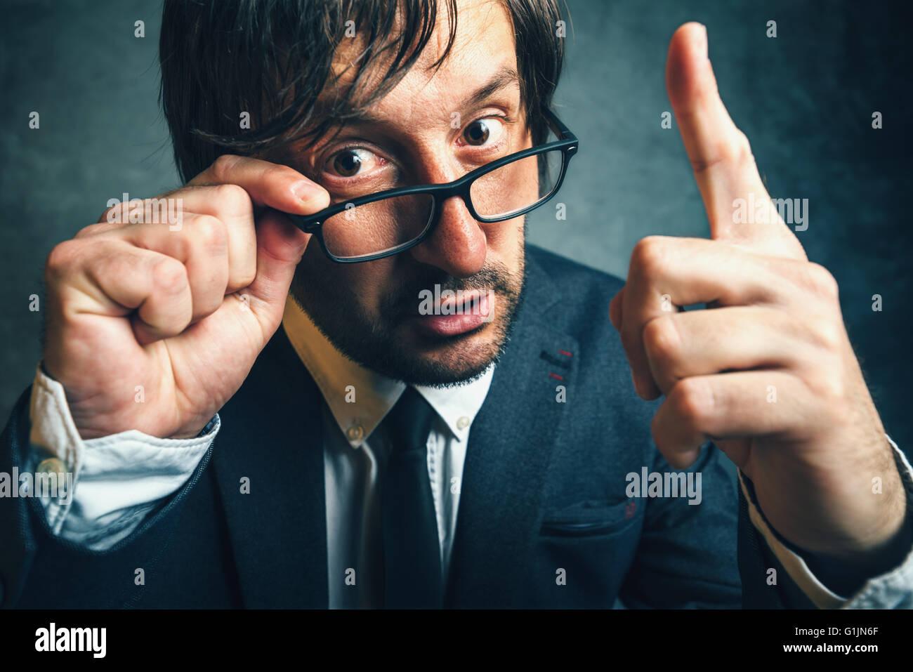 Enojado inspector fiscal busca seria y decidida, agresiva dedo amenazador empresario adulto con gafas Imagen De Stock