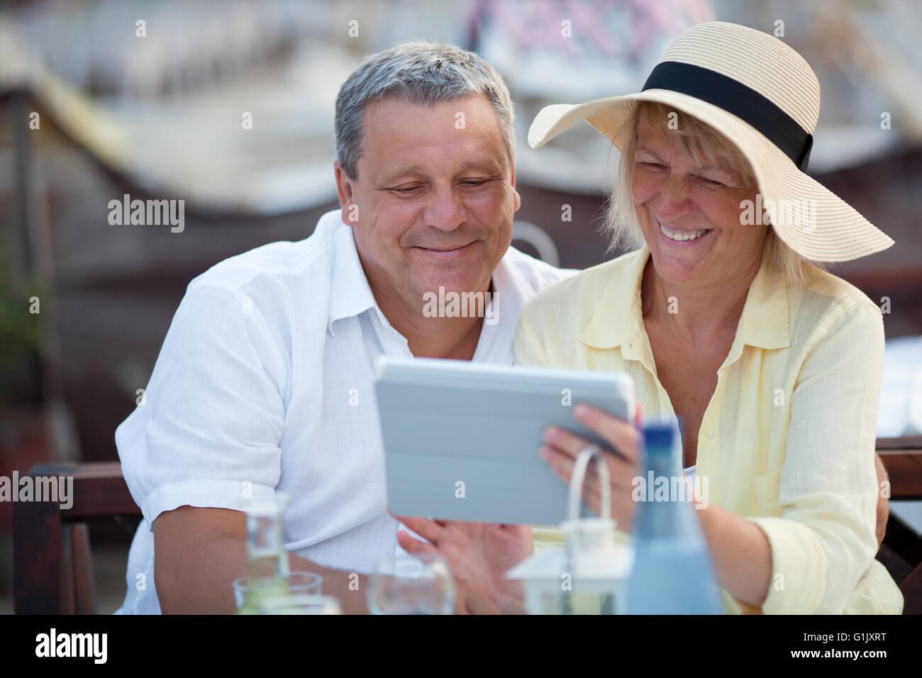 Sonriente pareja de mediana edad con un tablet Imagen De Stock