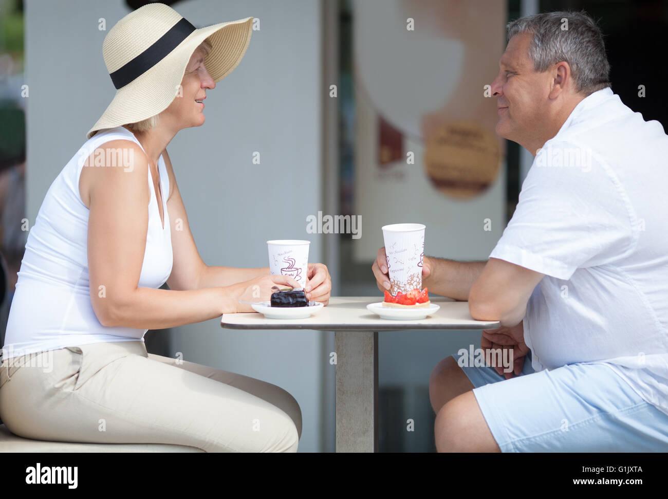 Vista lateral de dos ancianos sonrientes en la cafetería al aire libre Imagen De Stock
