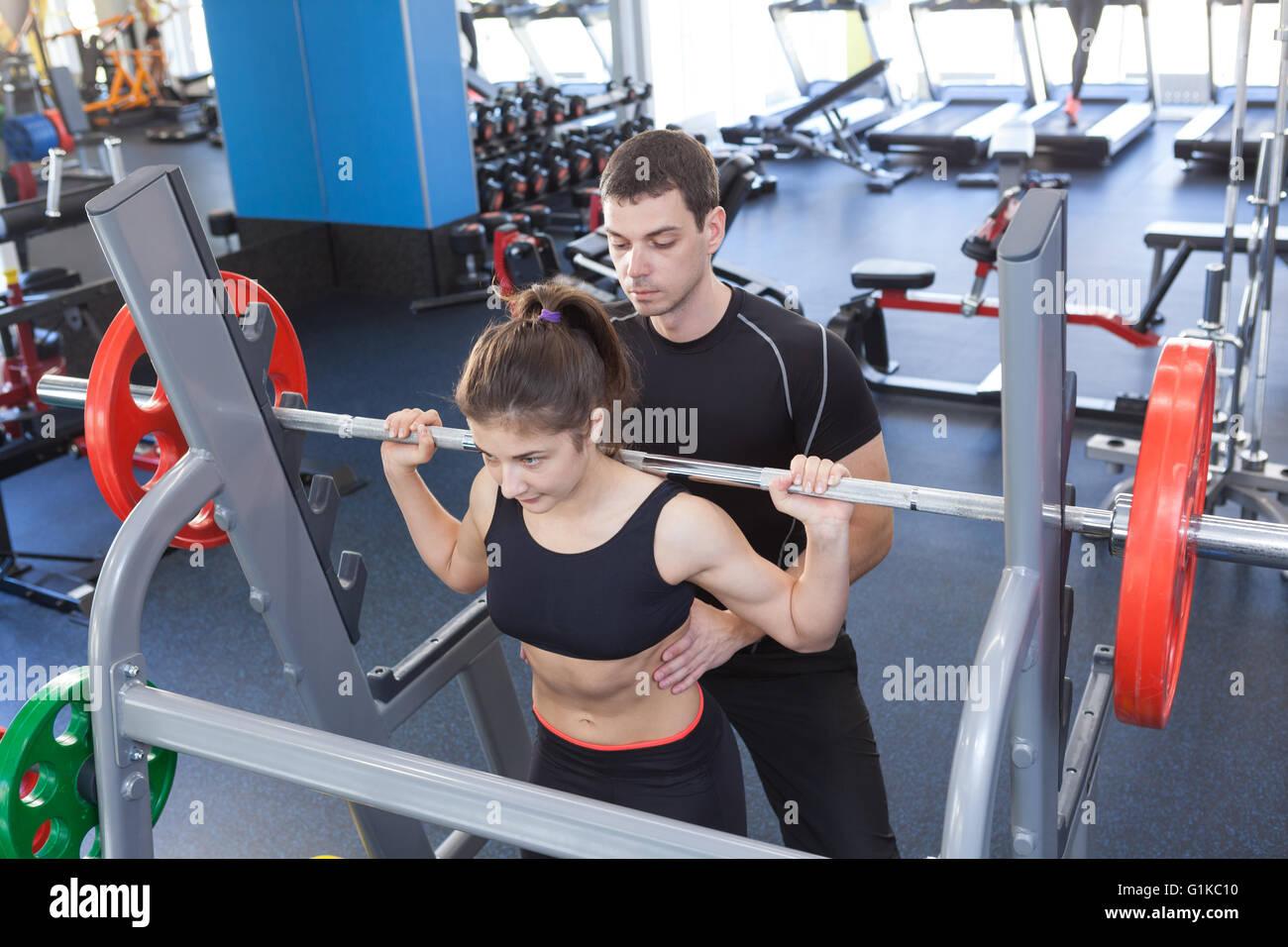 Mujer y entrenador personal de fitness en el gimnasio Imagen De Stock