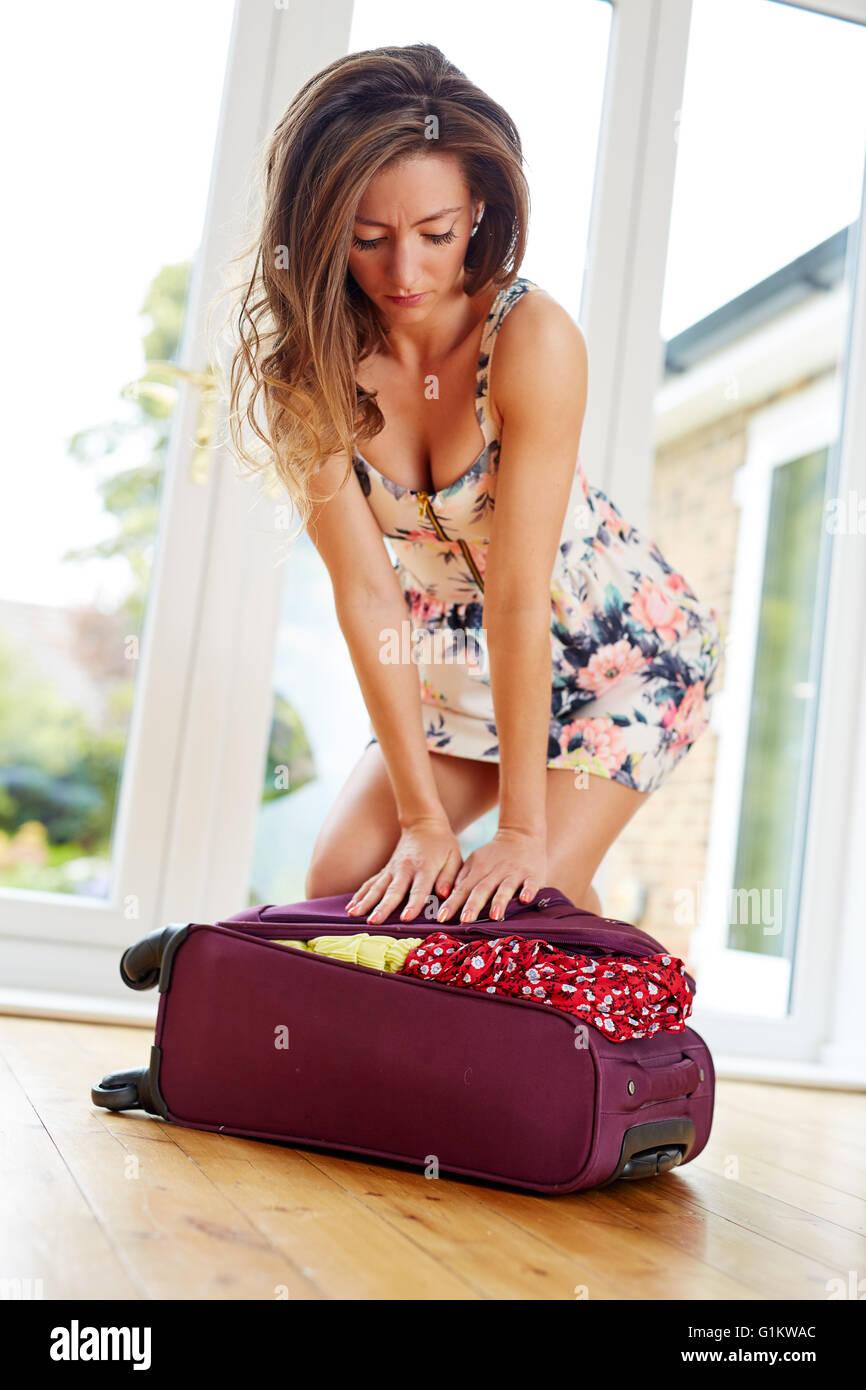 Chica luchando para cerrar maleta Foto de stock