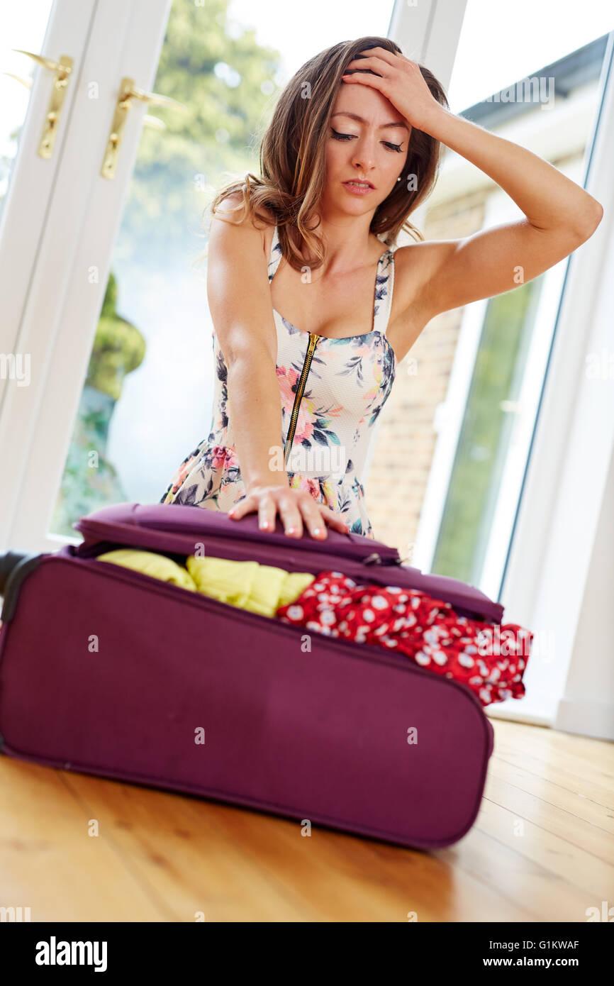 Chica luchando para cerrar maleta Imagen De Stock