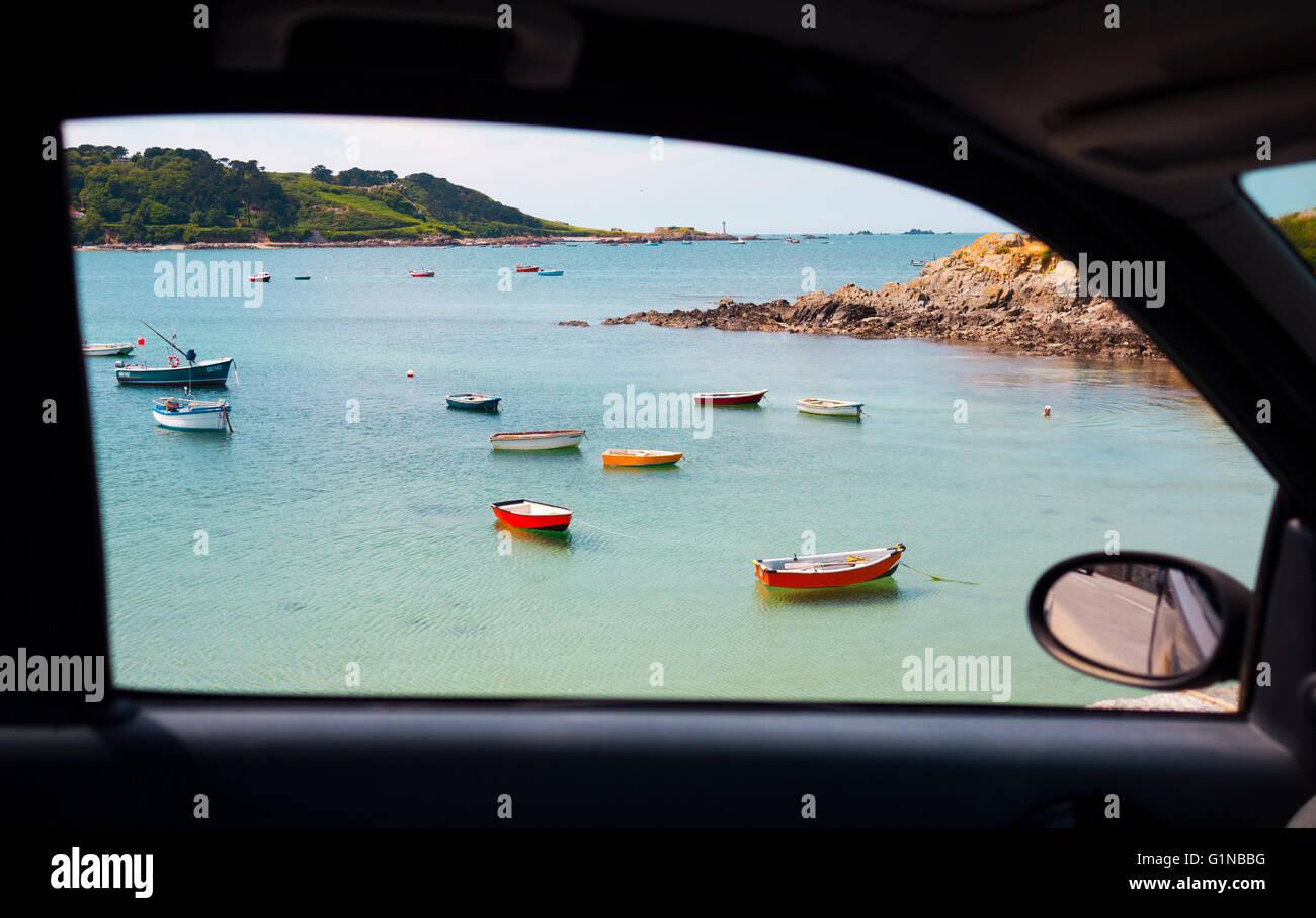 Vista única a una ventanilla de una pintoresca playa con barcos pesqueros en Guernsey, Islas del Canal de la Imagen De Stock
