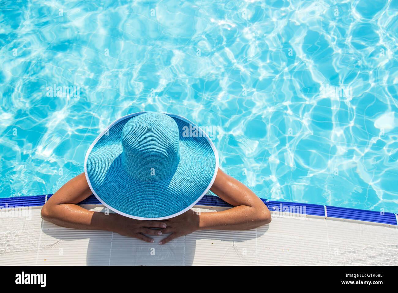 Mujer con sombrero para el sol en la piscina. Vista desde arriba. Foto de stock