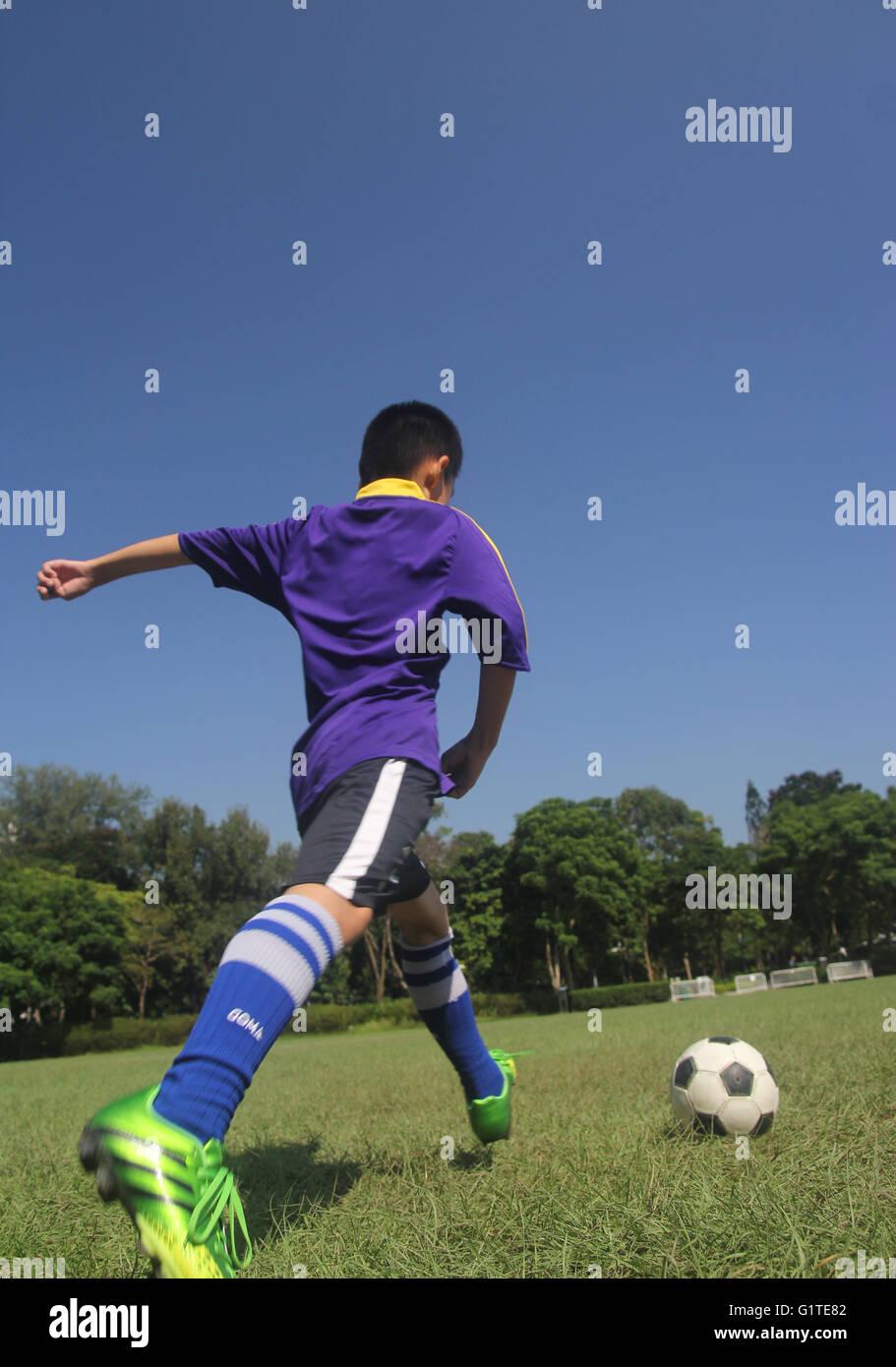 El niño goleador adolescente disparar ejercicio estimular hierba sun día shoot kick alto poder disparar Imagen De Stock