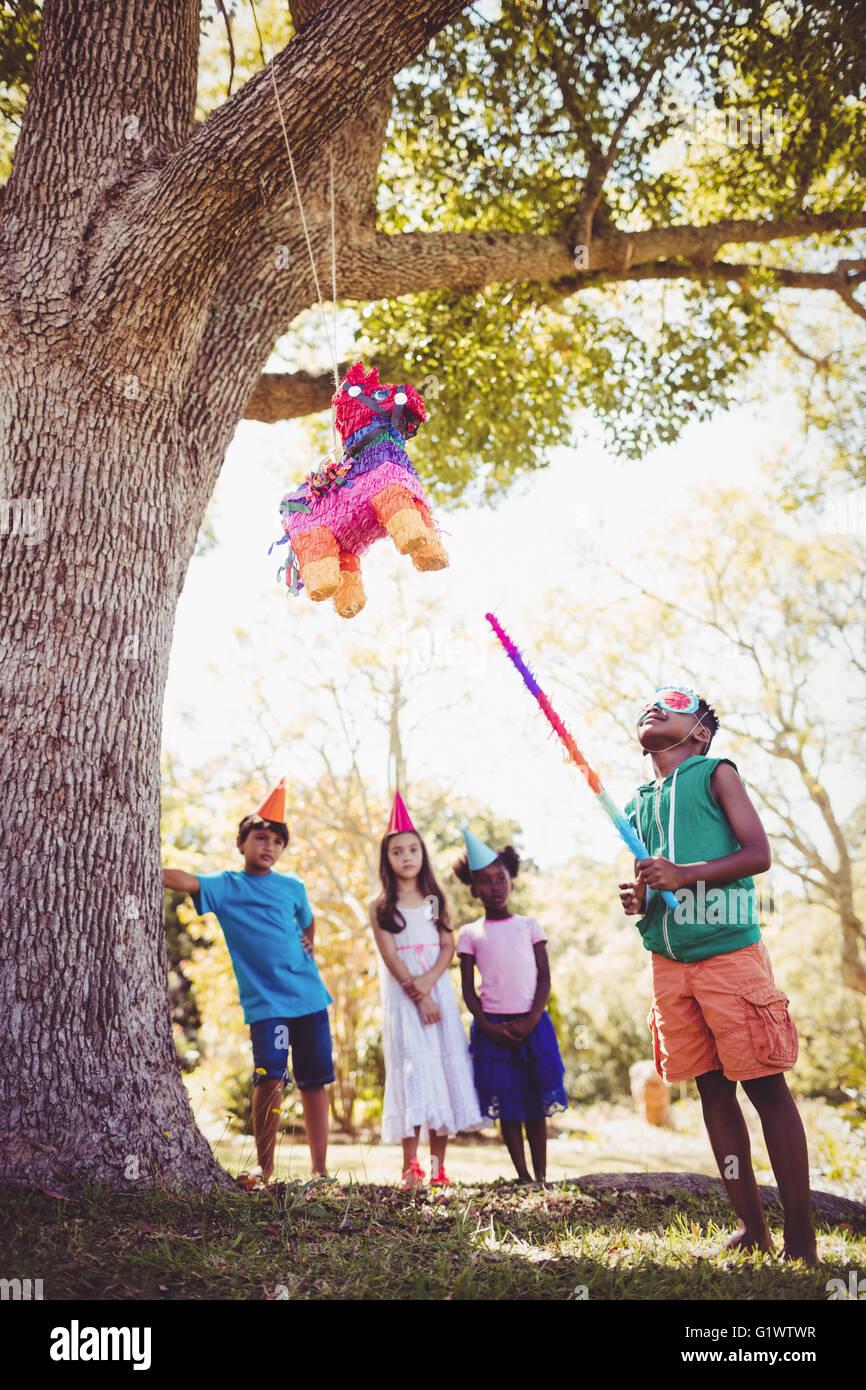Little Boy va a rompió una piñata para su cumpleaños. Imagen De Stock