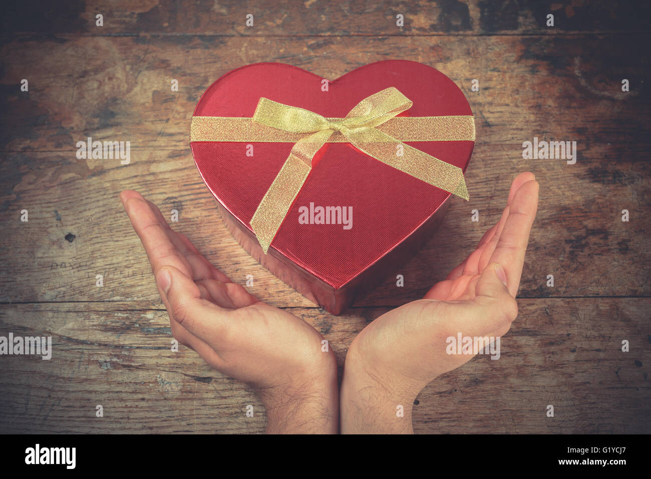 Un hombre de las manos descansan sobre una superficie de madera con una caja en forma de corazón Imagen De Stock