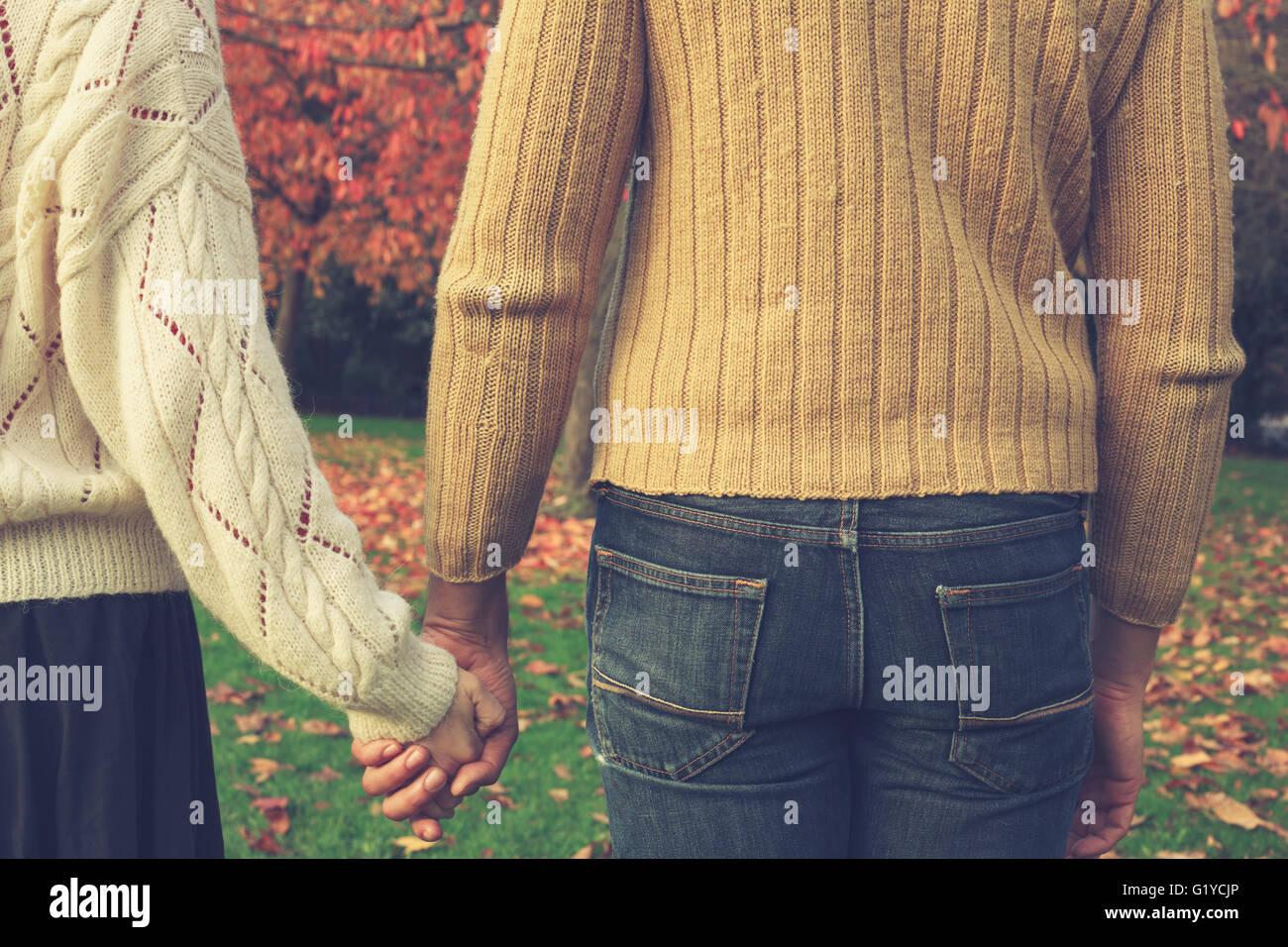 Una joven pareja está manteniendo las manos en el parque por un árbol en otoño Imagen De Stock