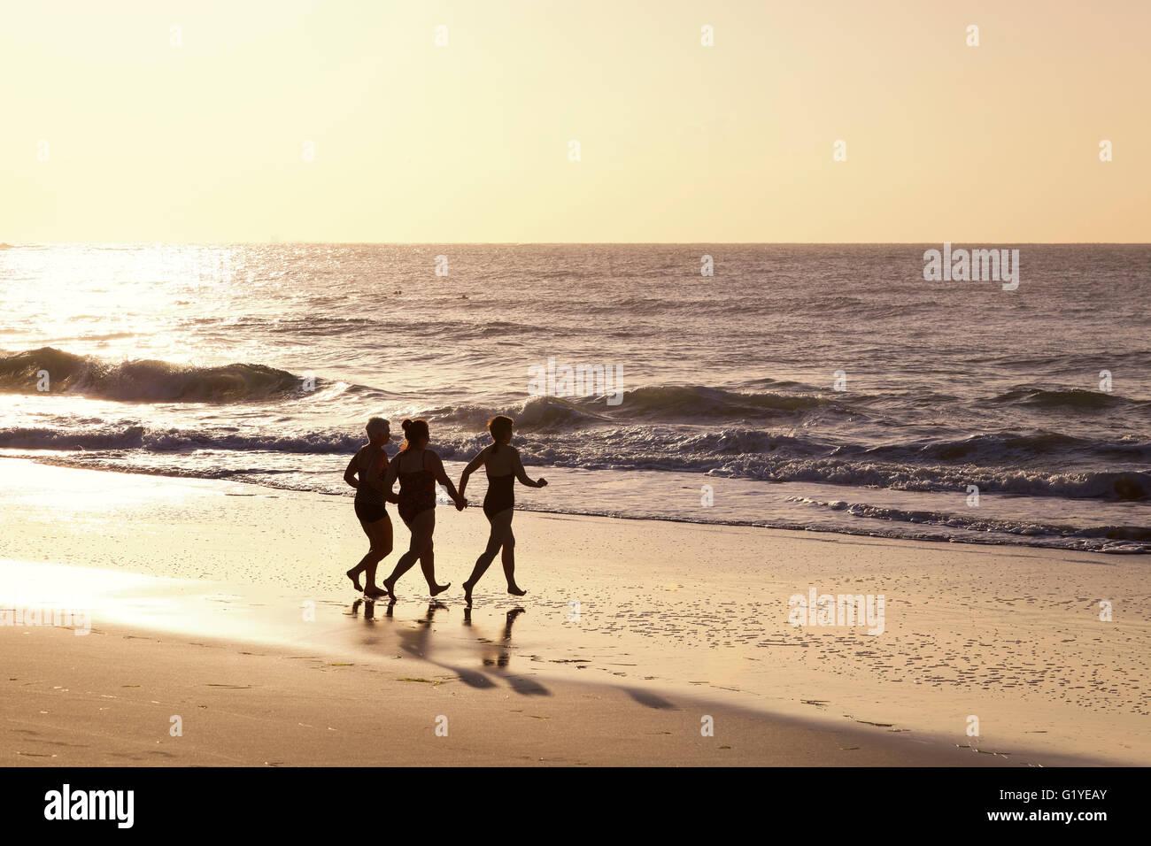 Tres mujeres corriendo en la playa en el agua con retroiluminación, Caloundra, Queensland, Australia Imagen De Stock