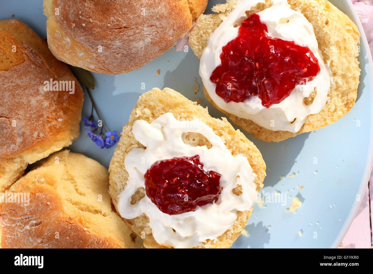 Scones escoceses con crema fresca y mermeladas de frambuesa cerrar Foto de stock