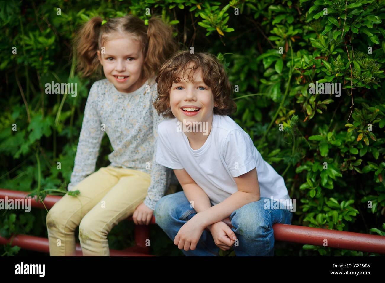 Chico Chica con sentarse en la valla en el parque y riendo Imagen De Stock