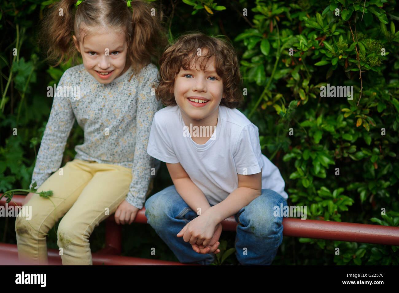 Chico y chica sentada en la valla cerca del arbusto verde Imagen De Stock