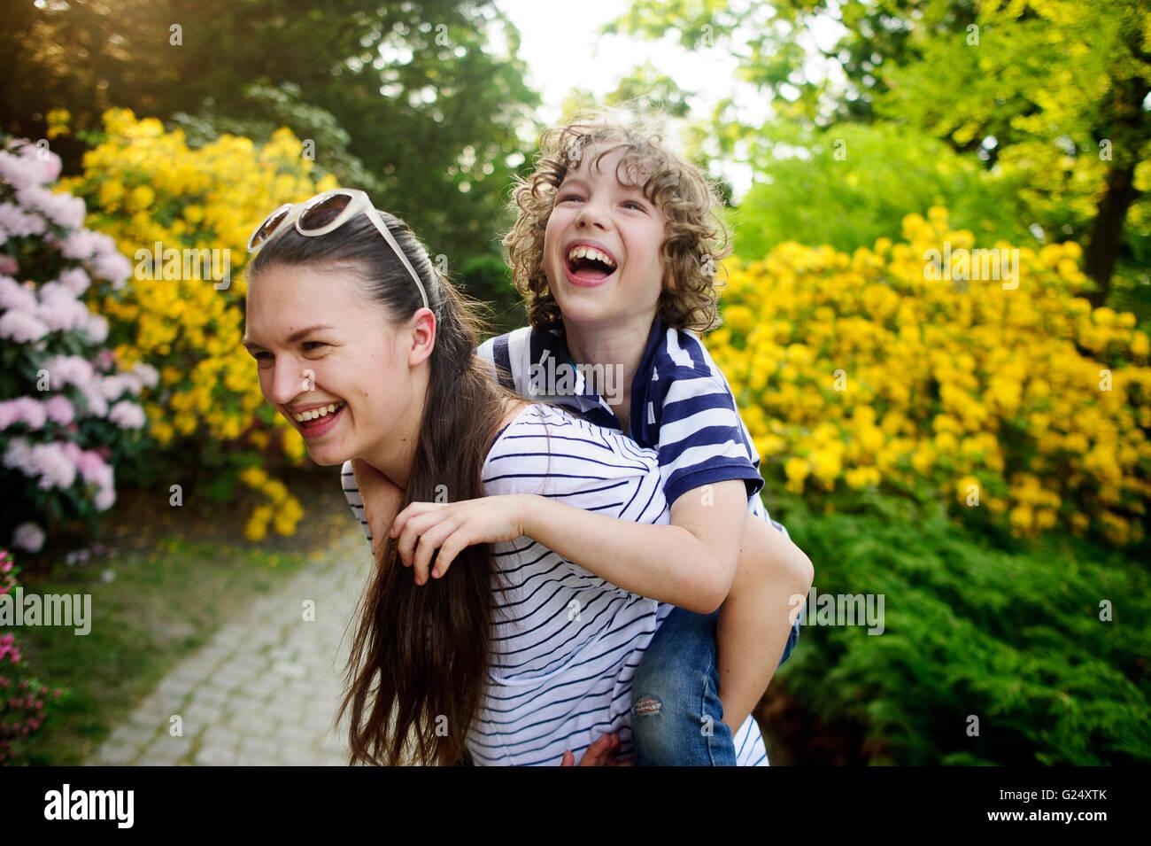 Hermana lleva sobre los hombros del hermano menor Imagen De Stock