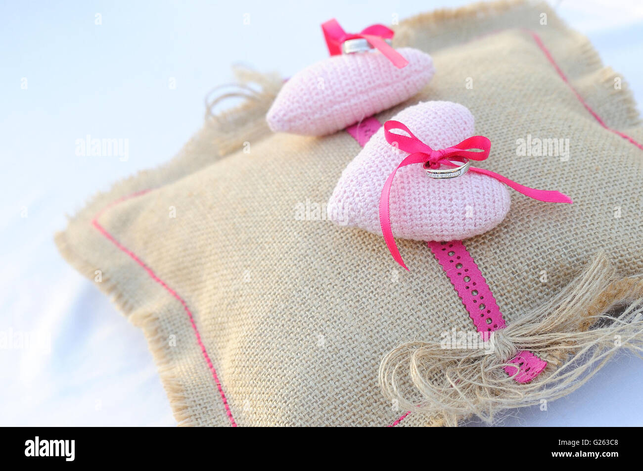 Anillos de compromiso sobre Arpillera almohada con dos corazones de color rosa Imagen De Stock