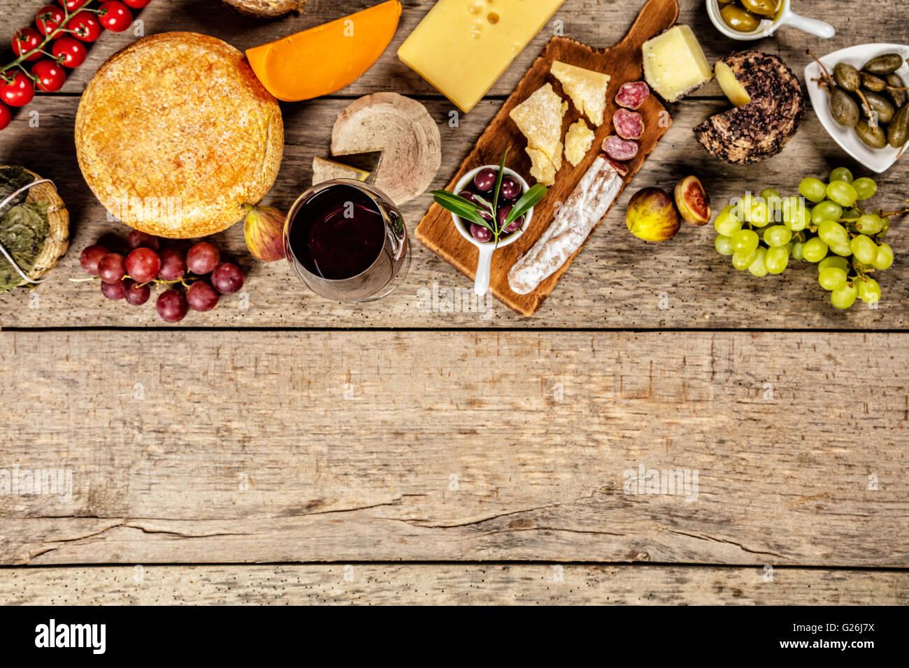 Diversos tipos de queso tradicional y la delicadeza adecuada para el vino, colocados sobre madera, disparado desde un alto ángulo de visualización. Foto de stock
