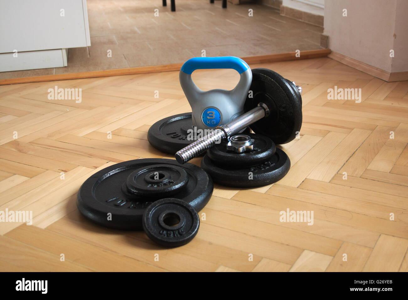 Herramientas para el hogar culturismo y fitness hervidora Bell y 40 Kg para ejercicios y pesas se colocan en parquet Imagen De Stock