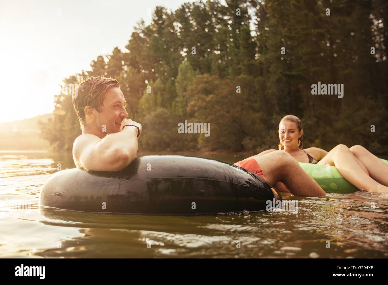 Retrato de joven feliz en el lago en el anillo hinchable con su novia. Pareja joven relajándose en el agua en un día de verano. Foto de stock