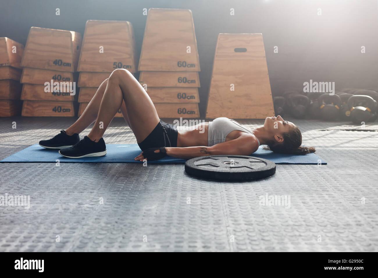 Vista lateral foto de mujer fitness descansando sobre colchoneta de ejercicios con un peso pesado de la placa en Imagen De Stock