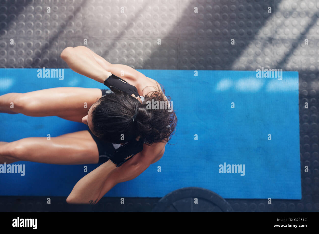 Vista aérea de mujeres trabajando en el gimnasio. Musculoso joven haciendo sentarse ups en una colchoneta de Imagen De Stock