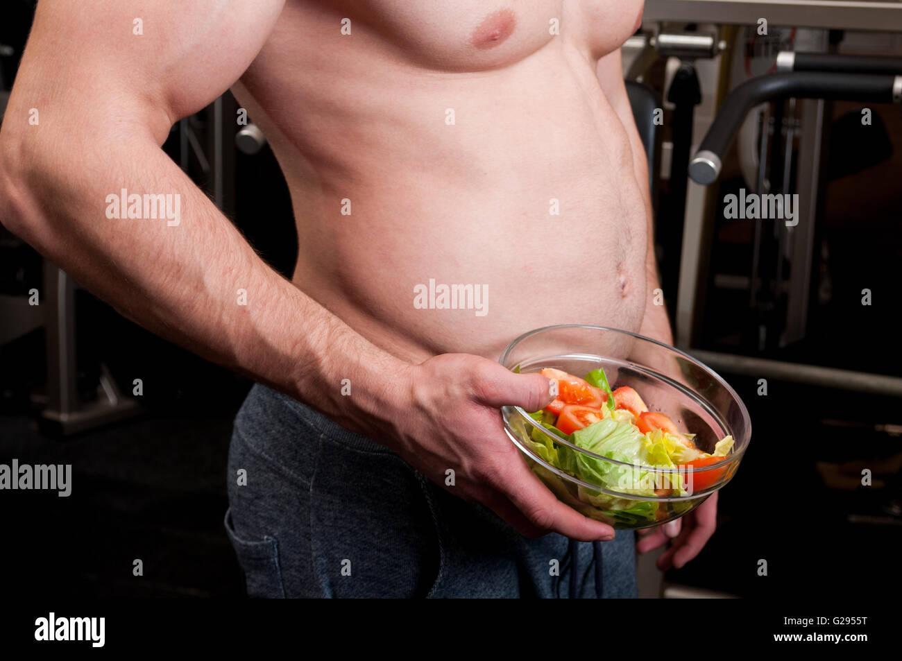 El edificio del cuerpo con big belly sosteniendo un cuenco de ensalada fresca Imagen De Stock
