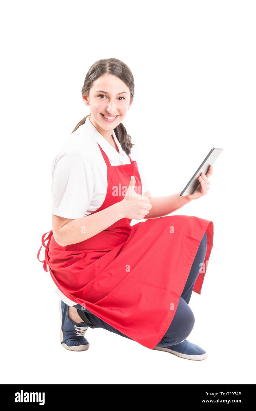 Hipermercado trabajadora mostrando el pulgar hacia arriba mientras mantiene tableta inalámbrica Imagen De Stock