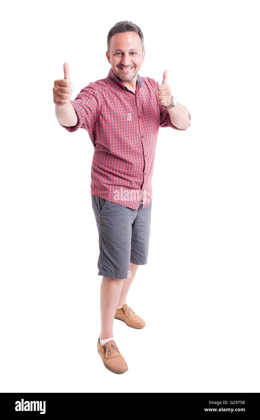 Hombre alegre mostrando Thumbs up. Viste pantalones cortos y camisetas de manga corta Imagen De Stock