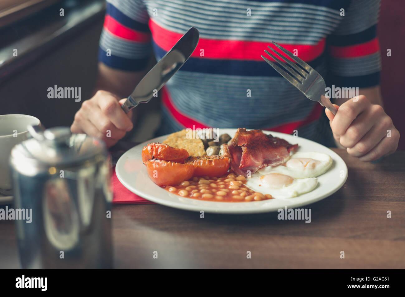 Una mujer joven está teniendo un tradicional desayuno inglés en un comedor Foto de stock