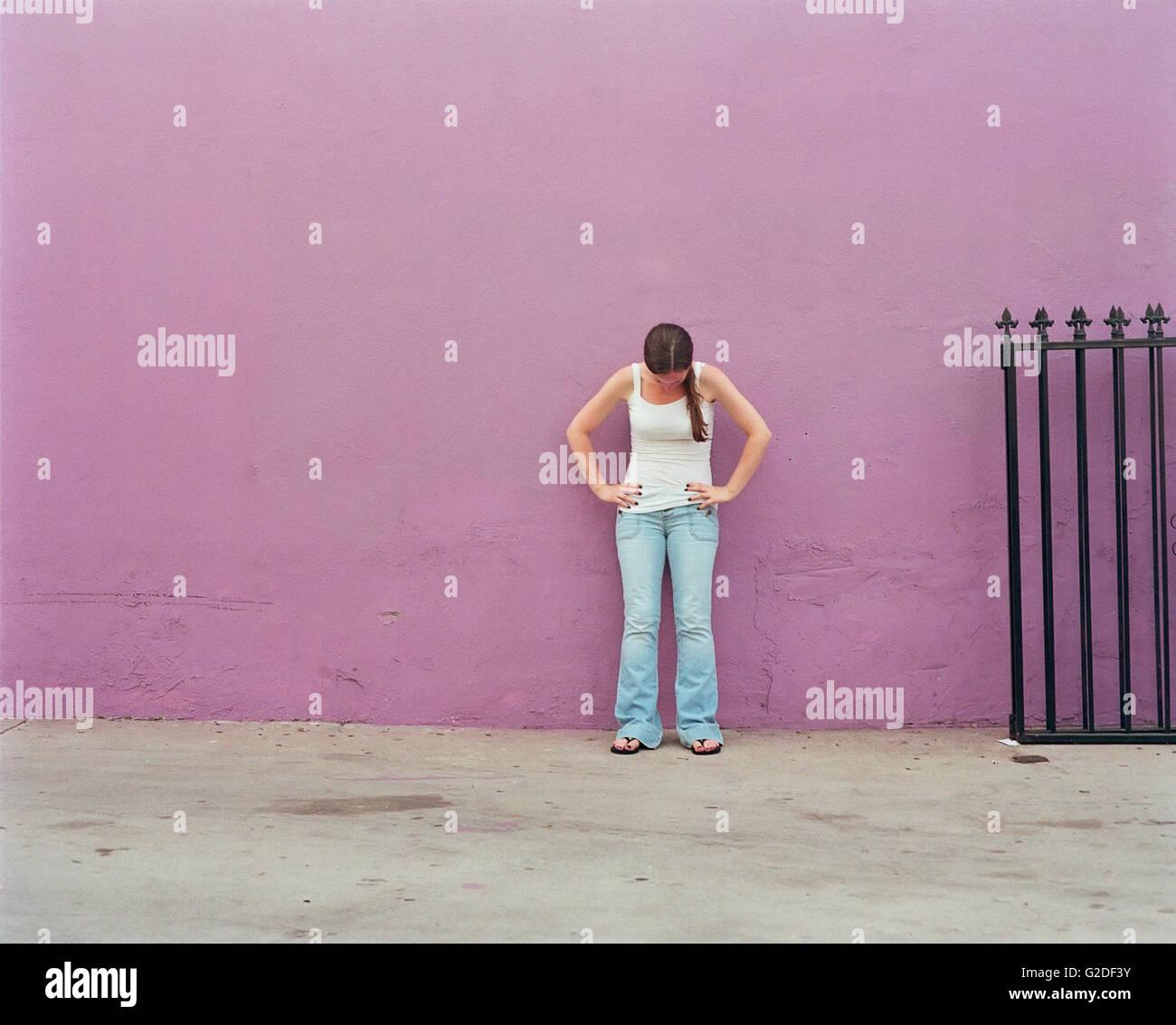 Mujer en el depósito superior y jeans de pie contra la pared púrpura con las manos en las caderas y mirando Imagen De Stock