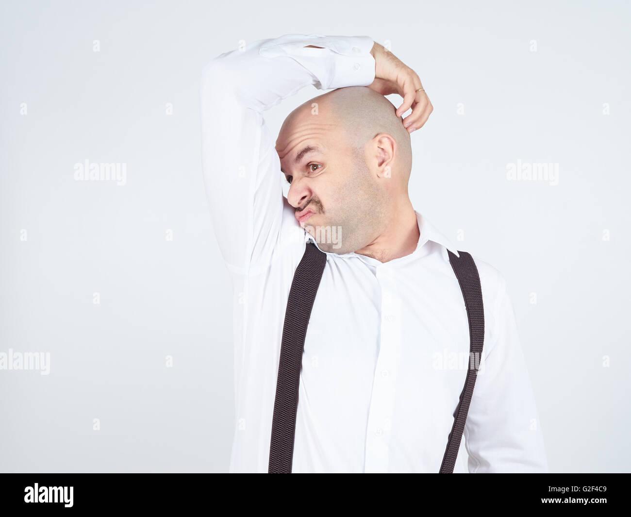 Hombre Calvo, oliendo olfateando su axila, algo huele mal, olor fétido aislado en el fondo. Imagen De Stock