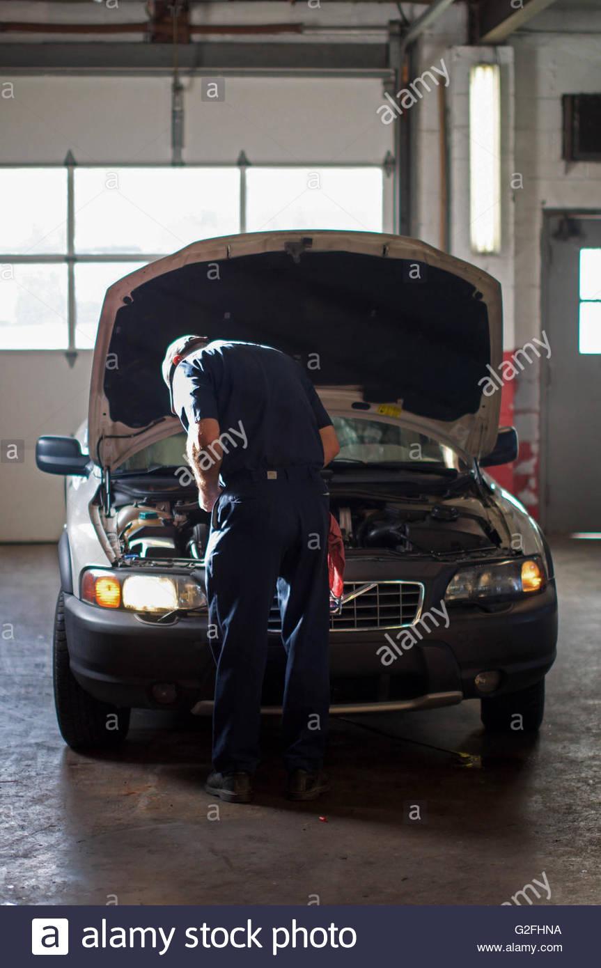 Mecánico que trabaja sobre el automóvil en el garaje, vista trasera Imagen De Stock