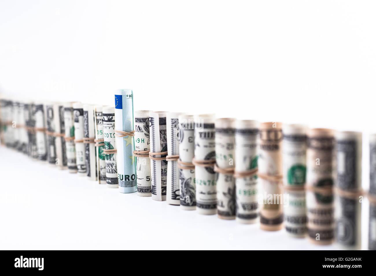 Fila de dollar rollos con un billete de euro en el medio aislado en blanco Foto de stock