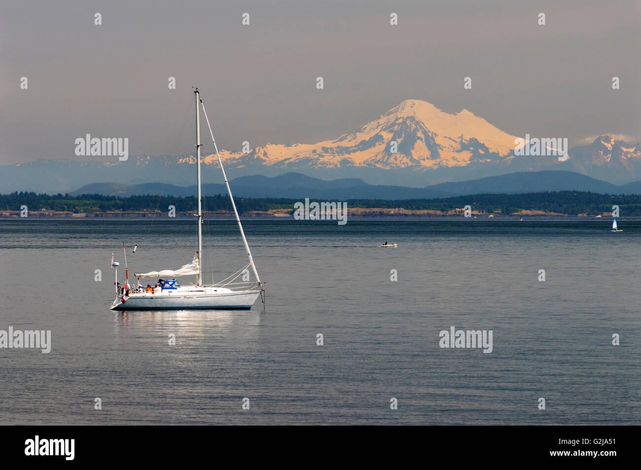 Un velero off sauces Beach en Oak Bay en Victoria, British Columbia. En el fondo es el Mt. Baker en el estado de Washington, EE.UU.. Foto de stock